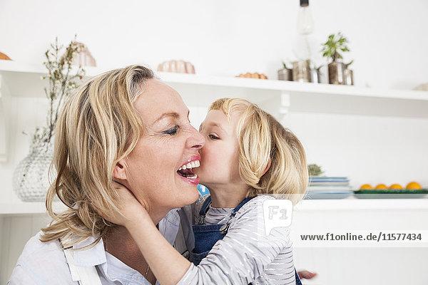 Mädchen küsst Mutter in Küche auf die Wange