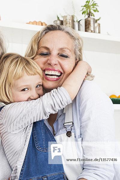 Porträt eines Mädchens  das seine Mutter in der Küche umarmt