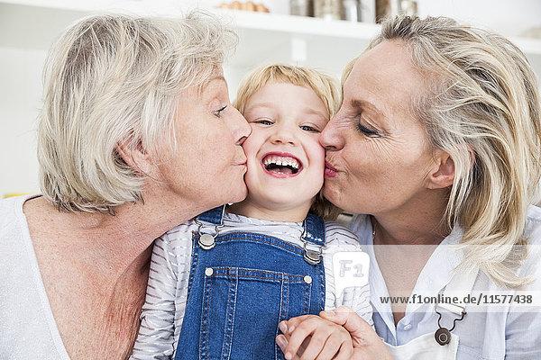 Porträt eines Mädchens  das von Mutter und Großmutter in der Küche auf die Wange geküsst wird