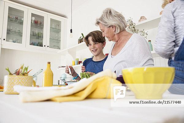 Ältere Frau bereitet mit Enkelkindern Gemüse am Küchentisch zu