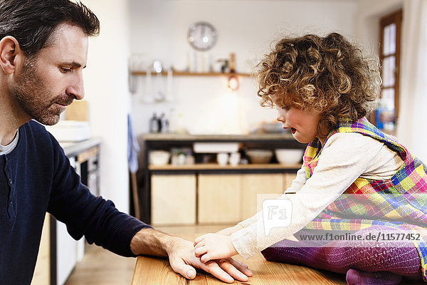 Girl on table sticking adhesive plaster onto father's hand