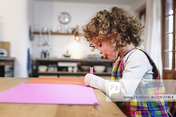 Mädchenzeichnung auf rosa Papier bei Tisch