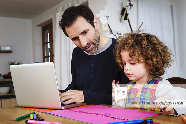 Girl Zeichnung am Tisch  während Vater mit Laptop