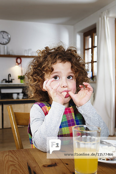 Girl sitting at table licking her thumbs after snack
