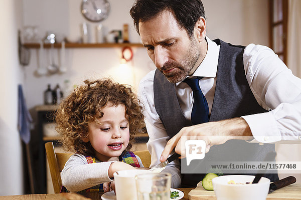 Man helping daughter with snack at table