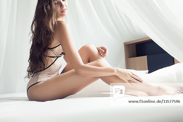 Porträt einer jungen Frau in Badebekleidung  die in provokanter Pose auf dem Bett sitzt