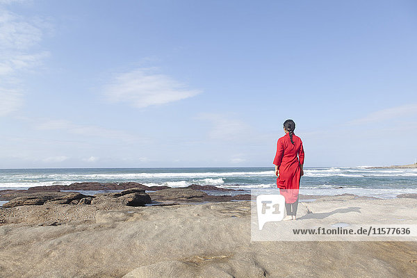 Woman wearing red dress  standing on rocks  looking at sea view  South Africa