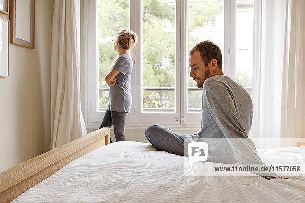Mittelgroßes erwachsenes Paar im Schlafzimmer  das Meinungsverschiedenheiten hat