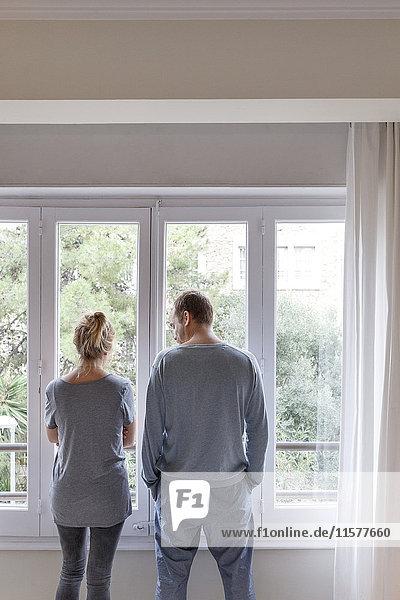 Mittleres erwachsenes Paar zu Hause  Blick aus dem Fenster  Rückansicht