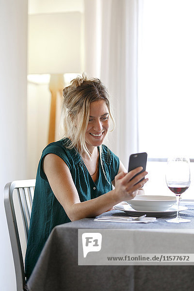 Woman sitting at diner table  using smartphone  smiling