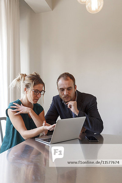 Mid adult couple sitting at table  looking at laptop