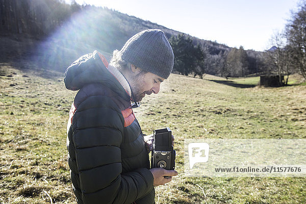 Man in rural setting  taking photograph with medium format camera  Italy