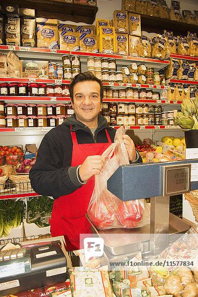 Porträt eines männlichen Lebensmittelhändlers  der in einem italienischen Lebensmittelgeschäft rote Paprika wiegt