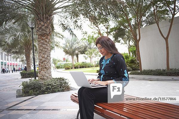 Reife Geschäftsfrau tippt am Laptop auf Parkbank  Dubai  Vereinigte Arabische Emirate