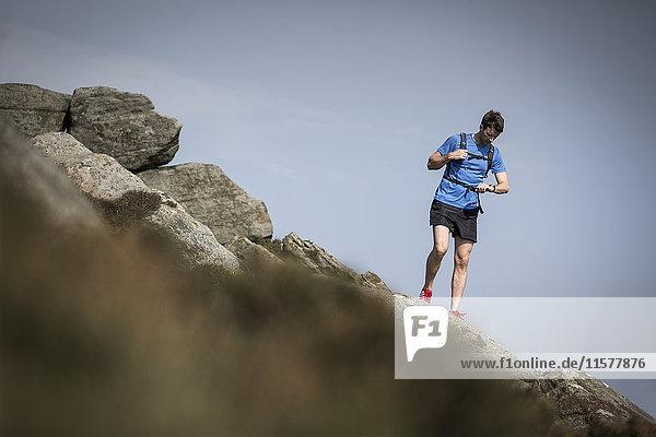 Männlicher Läufer schaut auf Smartwatch am Stanage Edge  Peak District  Derbyshire  UK