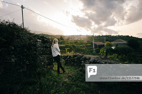 Woman looking out over vineyard landscape