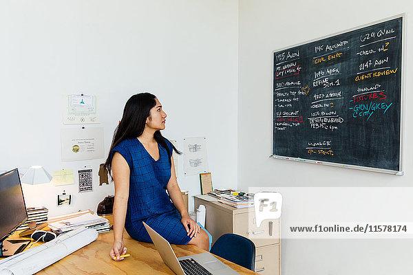 Frau sitzt im Büro auf dem Schreibtisch und schaut auf die Kreidetafel