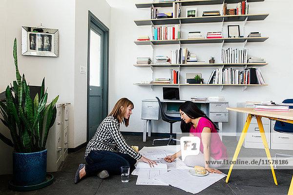 Kollegen in der Büroetage sehen sich Entwürfe an