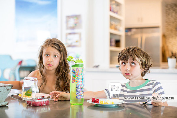 Boy and girl at kitchen table pulling faces