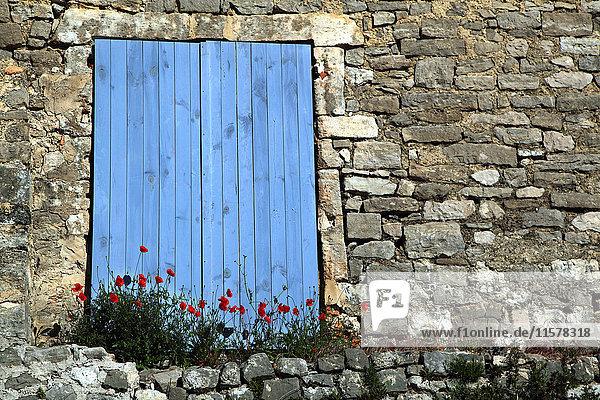 Frankreich Geschlossene blaue Fensterläden eines Steinhauses  Mohnblumen