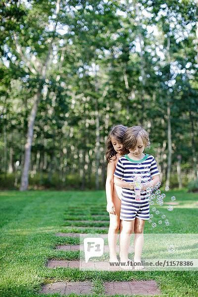 Mädchen und Junge beobachten Seifenblasen vom Spielzeugblasenmacher im Garten