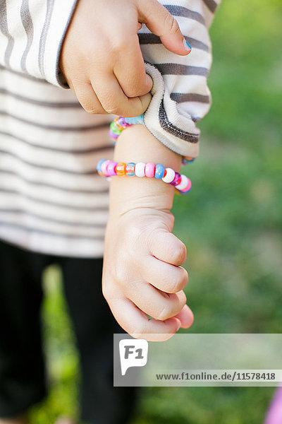 Schnappschuss eines Jungen  der den Ärmel hält und ein Armband zeigt