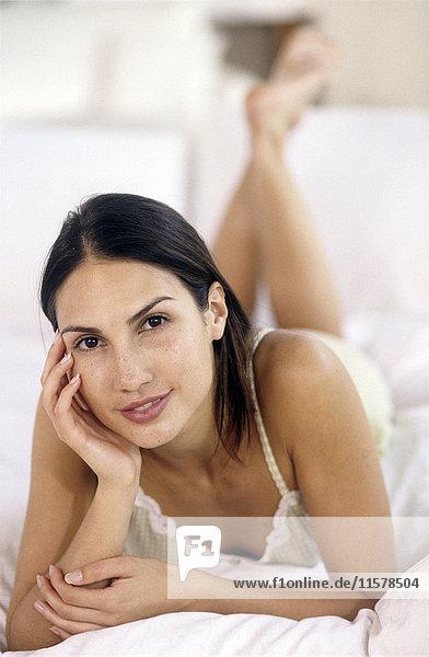 Junge brünette Frau liegt auf dem Bauch auf einem Bett und schaut mit erhobenen Beinen in die Kamera.
