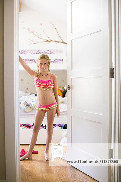 Mädchen im Bikini steht in der Tür