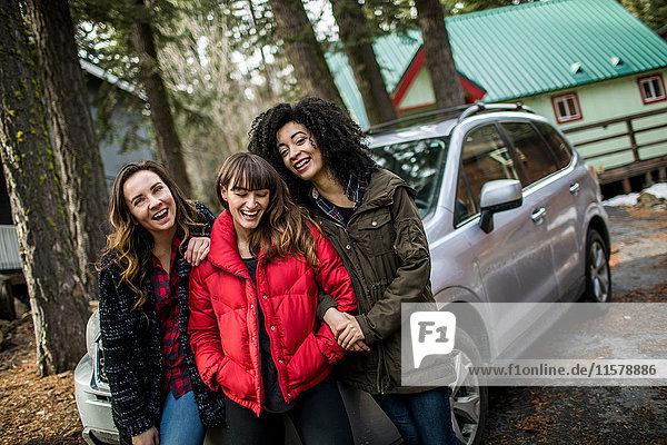 Porträt von drei Freunden neben dem Auto stehend  lachend
