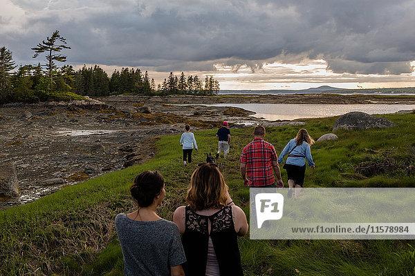 Rückansicht einer erwachsenen Familie zu Fuß zur Küste in Maine  USA
