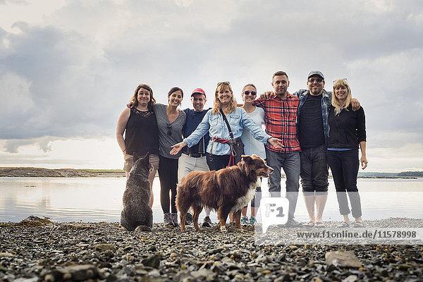 Porträt einer erwachsenen Familie und Hunden am Kiesstrand  Maine  USA