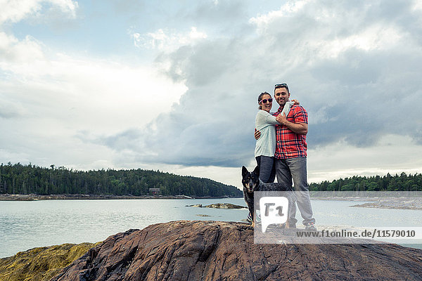 Portrait of romantic mid adult couple and dog on rock at coast of Maine  USA