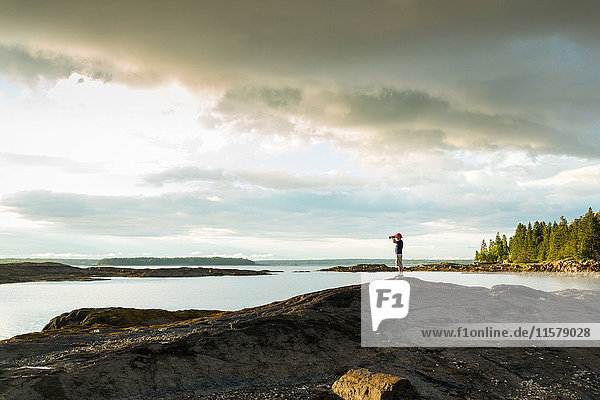 Distant view of senior man looking through binoculars at coast of Maine  USA