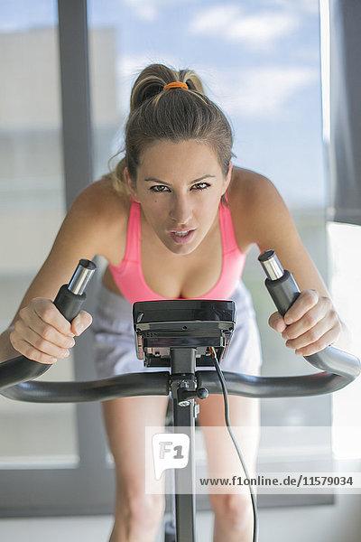 Hübsche Frau beim Spinning Bike im Fitnesscenter