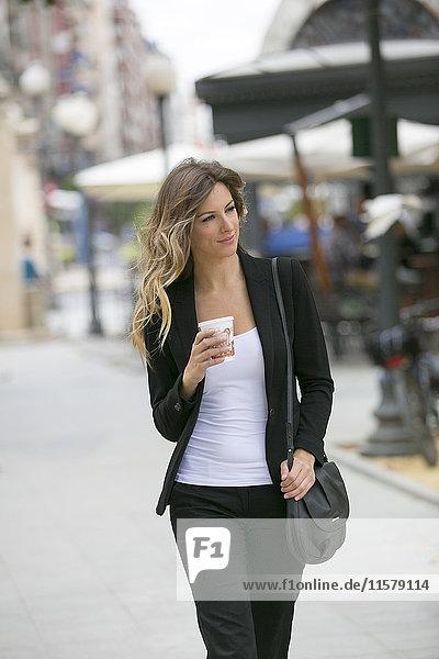 Hübsche Geschäftsfrau  die in der Innenstadt spazieren geht.