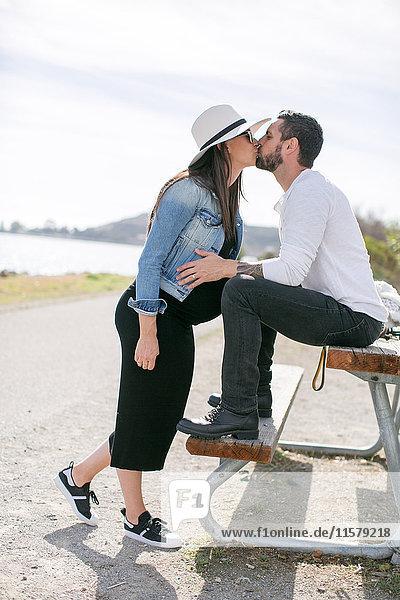 Schwangeres reifes Paar küsst sich auf Parkbank an der Küste
