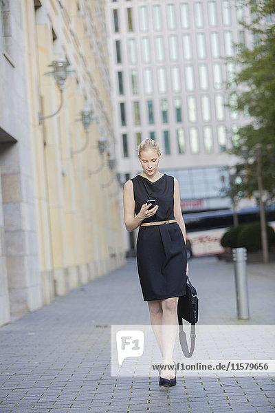Hübsche Geschäftsfrau mit Tasche  die ihr Handy in Downtown überprüft.