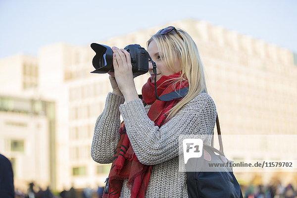 Hübsche blonde Frau mit Digitalkamera beim Fotografieren in einer Stadt in Europa