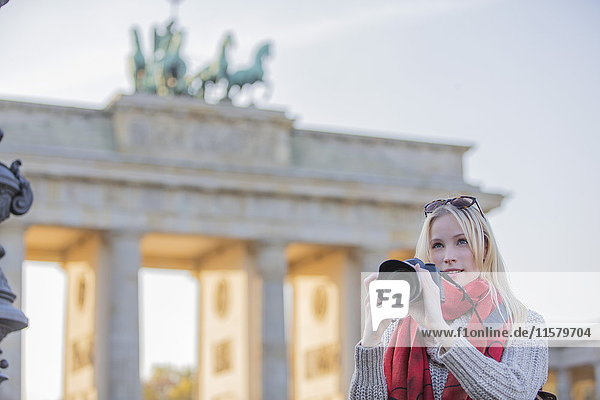 Hübsche blonde Frau fotografiert vor dem Brandenburger Tor in Berlin