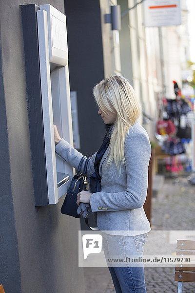 Hübsche blonde Frau an einem Geldautomaten.