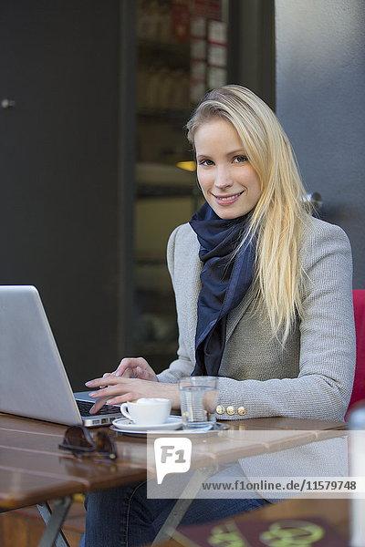 Hübsche blonde Frau mit Laptop in einem Cafe lächelnd vor der Kamera