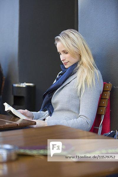 Hübsche blonde Frau liest ein Buch in einem Cafe in der Innenstadt.