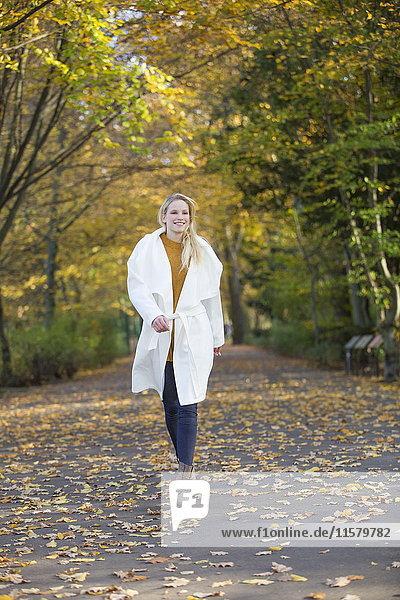 Hübsche blonde Frau  die im Herbst im Park spazieren geht.