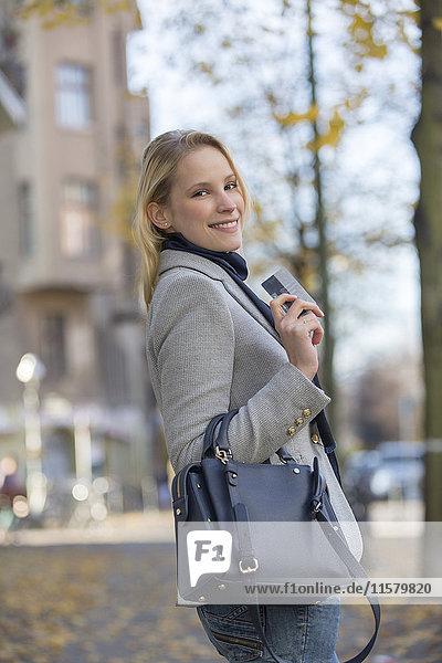 Hübsche blonde Frau beim Einkaufen und mit Bankkarte im Stadtzentrum