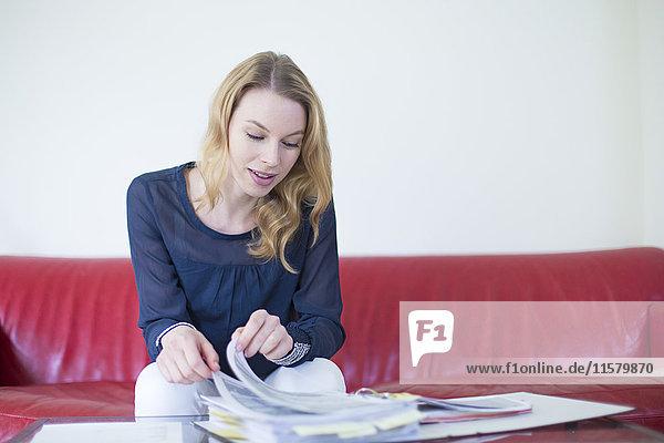 Hübsche blonde Frau  die zu Hause Rechnungen prüft.