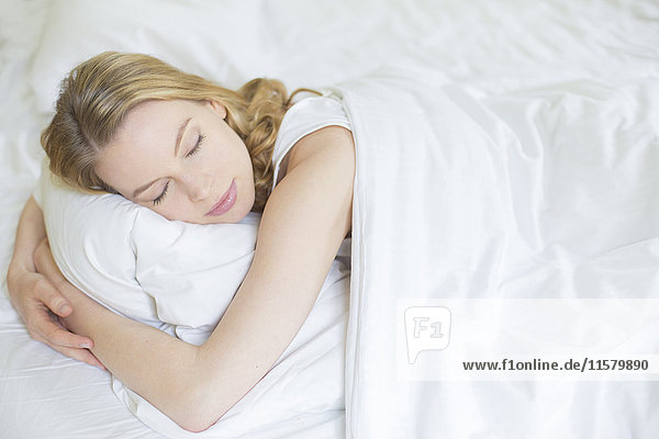 Hübsche blonde Frau  die im Bett schläft.