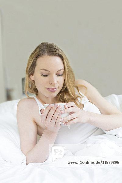Hübsche blonde Frau  die einen Tee im Bett genießt.