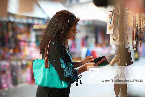 Mature female tourist looking beaded purse on market stall  Sharjah  United Arab Emirates