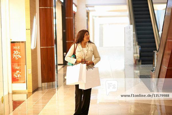 Ältere Frau trägt Einkaufstaschen in Einkaufszentrum  Dubai  Vereinigte Arabische Emirate