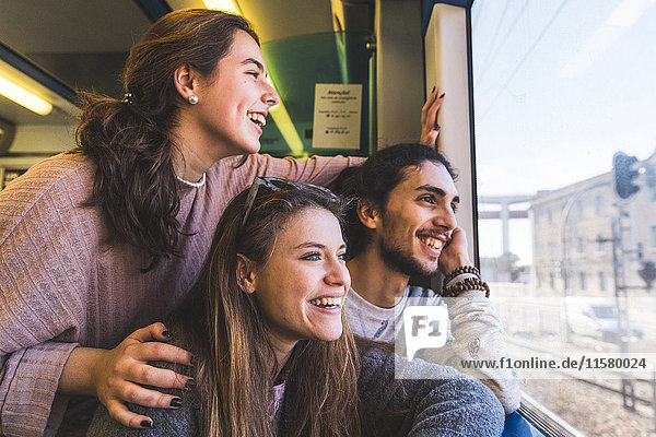 Three friends  on train  looking out of window at view  Lisbon  Portugal